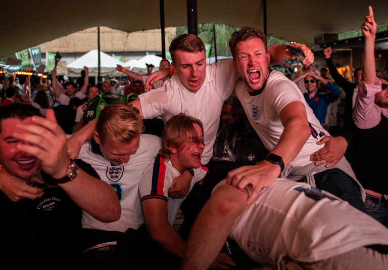 LONDON, - JULY 03: England football fans celebrate at Flat Iron Square as England score the second goal in their quarter final match against Ukraine on July 3, 2021 in London. England has reached the quarter-finals of Euro 2020 and is hoping for a win against Ukraine to take them to the semi-finals. (Photo by Chris J Ratcliffe/Getty Images)