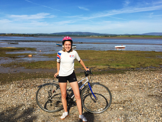Kezia Rice stands beside her bike on a summer day wearing cycling shorts