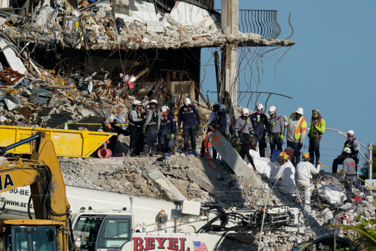 A team works to extricate remains as search and rescue personnel look on, atop the rubble at the Champlain Towers South condo building where scores of people remain missing more than a week after it partially collapsed