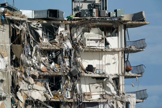 Furniture sits perched in the remains of apartments sheared in half, in the still standing portion of the Champlain Towers South condo building