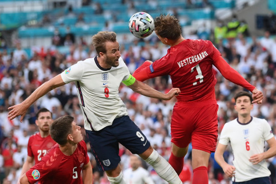 England's Harry Kane, left, jumps for the ball with Denmark's Jannik Vestergaard during the Euro 2020 soccer semifinal match between England and Denmark at Wembley stadium in London, Wednesday, July 7, 2021. (Laurence Griffiths/Pool Photo via AP)