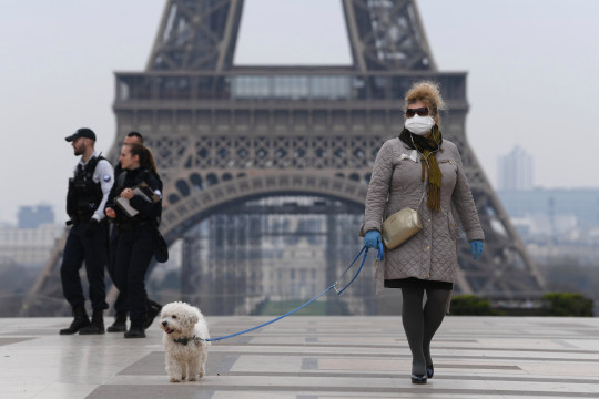PARIS, FRANCE - MARCH 18: A woman wears protective gloves near the Eiffel tower the second day after the announcement by French President Emmanuel Macron of the confinement of the French due to an outbreak of coronavirus pandemic (COVID-19) on March 18, 2020 in Paris, France. From Tuesday, March 17 at noon for at least two weeks, the French will have to stay at home, under penalty of sanctions, unless travel is absolutely necessary, announced the head of state. President launched the war against the coronavirus and placed France in containment without ever saying the word. The Coronavirus epidemic has exceeded 7,900 dead for more than 198,000 infections across the world. (Photo by Pascal Le Segretain/Getty Images)