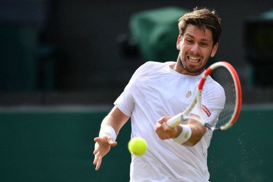 Cameron Norrie returns against Switzerland's Roger Federer during their men's singles third round match on the sixth day of the 2021 Wimbledon Championships at The All England Tennis Club in Wimbledon, southwest London, on July 3, 2021.