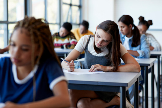 Young multi-ethnic female students writing exam while sitting at desk in examination hall
