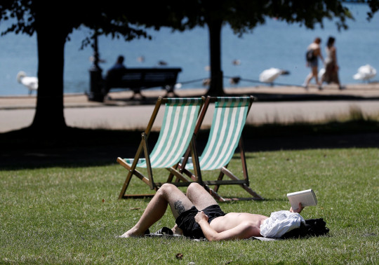 A man relaxes in the warm weather in Hyde Park, London, Britain, July 16, 2021. REUTERS/Peter Nicholls
