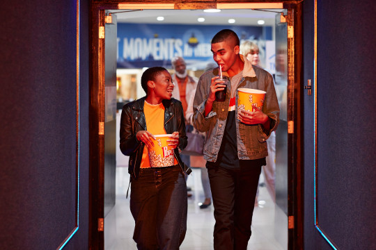 Happy young friends talking while walking in corridor at movie theater