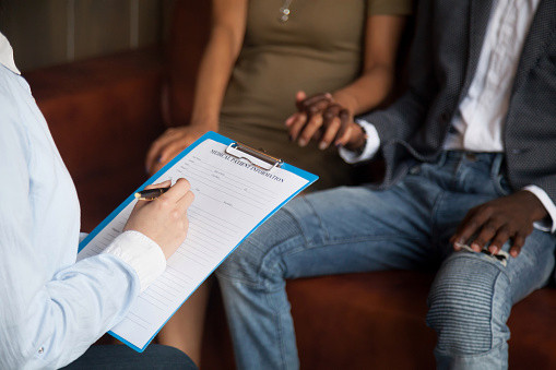 Close up of an anonymous white medical person filling a medical patient information form, while an anonymous Black couple holds hands as they sit in front of them.