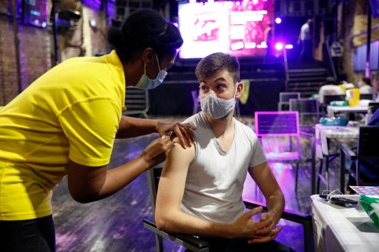 LONDON, ENGLAND - AUGUST 08: A man receives a dose of the Pfizer vaccine at an NHS Covid-19 vaccination centre hosted at the nightclub Heaven on August 8, 2021 in London, England. From late September, the UK government plans to require that patrons show proof of full vaccination to enter nightclubs. (Photo by Hollie Adams/Getty Images)