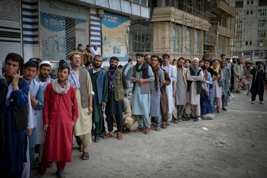 TOPSHOT - Afghans queue up as they wait for the banks to open and operate at a commercial area in Kabul on August 31, 2021. (Photo by Hoshang Hashimi / AFP) (Photo by HOSHANG HASHIMI/AFP via Getty Images)