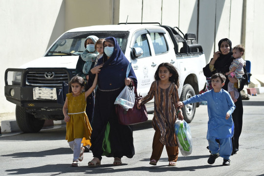 Afghan woman with children, hoping to leave Afghanistan, walk through the main entrance gate of Kabul airport in Kabul on August 28, 2021, following the Taliban stunning military takeover of Afghanistan. (Photo by WAKIL KOHSAR / AFP) (Photo by WAKIL KOHSAR/AFP via Getty Images)