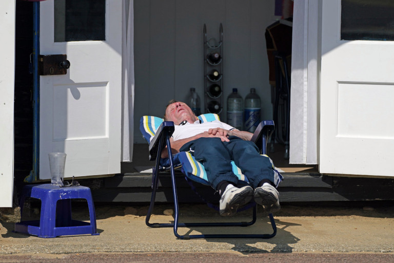 A man enjoys the warm weather on Bournemouth seafront in Dorset. Picture date: Monday September 6, 2021. PA Photo. See PA story WEATHER Hot. Photo credit should read: Steve Parsons/PA Wire