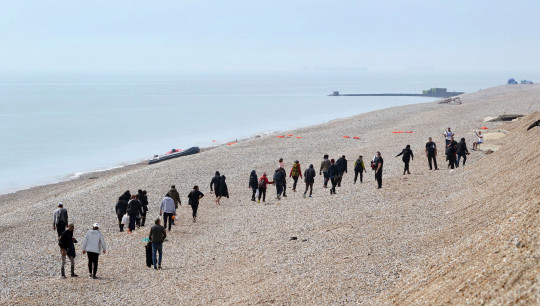 A group of people thought to be migrants are escorted along the beach after arriving in a small boat at Dungeness in Kent.