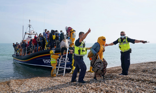 A group of people thought to be migrants are brought ashore from the local lifeboat at Dungeness in Kent.