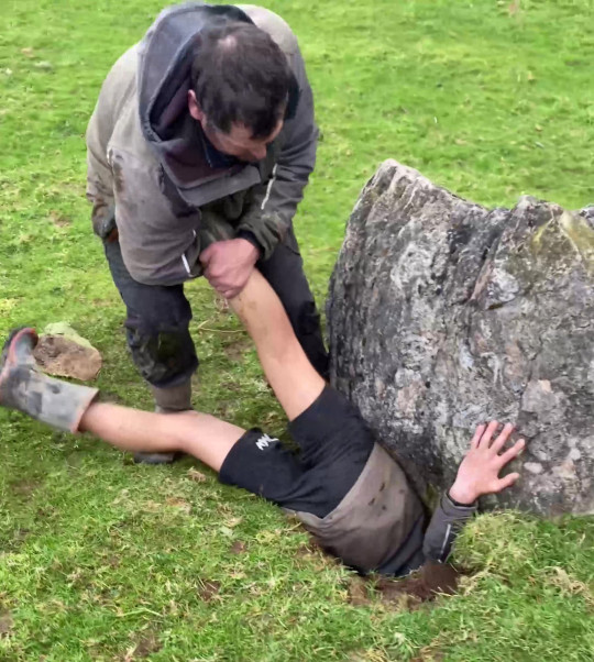PIC FROM Kennedy News/Ripples Retreat (PICTURED:CORBAN DENIZE, 14, REACHING INTO THE HOLE TO SAVE THE LAMB AS DAD BRENDAN DENIZE HOLDS ONTO HIM) This is the heroic moment a courageous teen burrowed into a 7ft-deep hole beneath a giant rock to pull a trapped lamb to safety - after being overcome by a 'sixth sense' calling him to save it. Corban Denize, 14, rushed to investigate with dad Brendan Denize and sister Katie Denize when his grandad told them a worried ewe was lingering around a rock last Sunday morning [AUGUST 29]. When there were no signs of life they gave up looking down a small hole, but a 'feeling they hadn't done enough' came over them, triggering them to widen the crevice and continue. DISCLAIMER: While Kennedy News and Media uses its best endeavours to establish the copyright and authenticity of all pictures supplied, it accepts no liability for any damage, loss or legal action caused by the use of images supplied and the publication of images is solely at your discretion. SEE KENNEDY NEWS COPY - 0161 697 4266