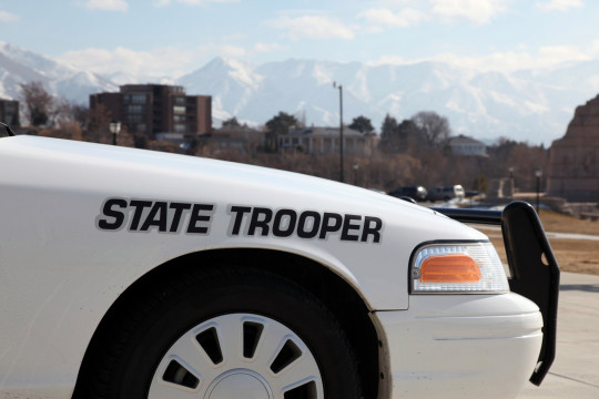 DSLR picture of a white state trooper police car in front of an office building. The sky is blue with few clouds and there is city buildings and mountains in the background.