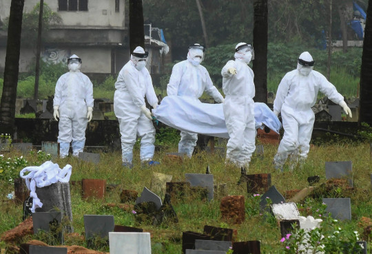 People in protective suits prepare to cremate the body of a 12-year-old boy died of the Nipah virus in Kozhikode, Kerala state, India, Sunday, Sept.5, 2021.